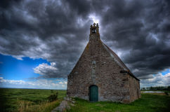 Dark clouds over rural church. Scenic view of dark cloudscape over old church in countryside royalty free stock photos