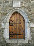 Old church door. Wooden door contrasting with the old brickwork on a church.  Desmonds Castle in Kinsale, Ireland which was once used as a french prison Royalty Free Stock Photo