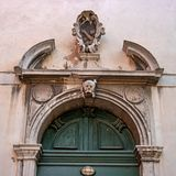Old Church door in Venice. Fragment. Italy. The door is decorated with bas-reliefs and decorative elements. Above the. Door is a skull sculpture Royalty Free Stock Photos
