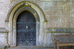 Old church door. This door is very old, 17th Century. It's the front door to an old english church. In front of the church is a bench where you can meditate Royalty Free Stock Photography