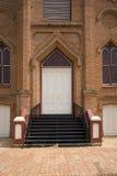 Old church doors. Brick sidewalk and white church doors Royalty Free Stock Photo