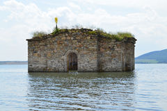 Old church engulfed in the water of dam lake. Silhouette of flooded small Orthodox church in the waters of large lake, Zhrebchevo dam was built during the Soviet Royalty Free Stock Image