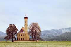 Old church with high bell tower and graveyard bellow mountains. Royalty Free Stock Images