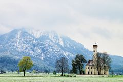 Old church with high bell tower and graveyard bellow mountains. Stock Images