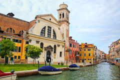 Old church and houses on a narrow canal in Venice, Italy. Stock Photos