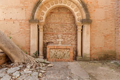 Old church. Image of the part of an old church, stoned statue of the woman under the arch near the fallen tree Stock Photography