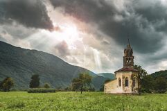 Free Old Church In The Mountains With Sun Rays Shining Through The Cloudy Sky Stock Images - 212013324
