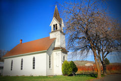 Old Church Landmark. A side view of a charming old church with a large steeple under clear blue skies Stock Images
