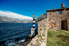 Old church and lighthouse in Kotor bay Royalty Free Stock Images