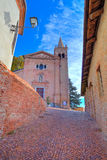 Old church and narrow street. Monticello D'Alba, Italy. Vertical image of  red brick church and narrow cobblestone street in at medieval part of the town in Royalty Free Stock Photos
