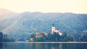 Old church on small island in the middle of lake with gondolas flowing on watter, Bled Lake Slovenia royalty free stock photography