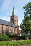 Old church with steeple. Exterior of old stone church with spire or steeple, tree and garden in foreground Royalty Free Stock Images