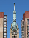 Old church steeple and buildings. Old, tall and steep Christian church steeple spire between two modern buildings.  Isolated against a blue sky Stock Photo
