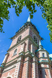 Old Church in Stockholm Framed by a Green Leafcover. Old Church (Tyska Kyrkan) In Gamla Stan, Stockholm, Standing Against a Blue Sky Framed By a Large Green Royalty Free Stock Photo