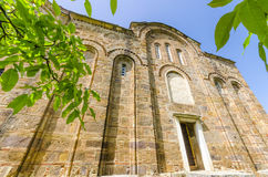 Old church stone walls, Macedonia. View of church stone wall with arc windows on bright blue sky.Beautiful perspective and tree green branches Royalty Free Stock Images