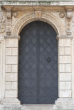 Old church textured door with stone arch facade. Krakow Stock Photo
