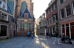 Old church and tourists on the street at the red light district. AMSTERDAM, NETHERLANDS - MAY 5, 2016: City view with the Old churchOude Kerk and tourists on the royalty free stock image