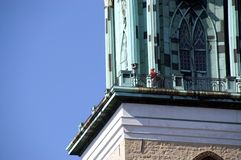 Old church tower. Low angle view of old church tower with person on balustrade, blue sky background stock photo