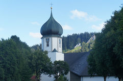 Old church tower and modern ski jumps Stock Images