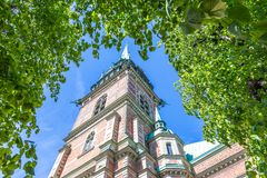 Old Church (Tyska Kyrkan) in Stockholm. Old Church (Tyska Kyrkan) In Gamla Stan, Stockholm, Standing Against a Blue Sky Framed By a Large Green Leafcover Stock Photography