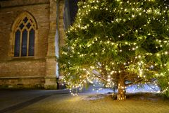 Old Church Window and Christmas Tree. An old church window is illuminated by the fairy lights on a large Christmas tree, creating a peaceful and friendly Stock Photo
