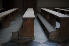 Old church wooden benches with poor light in empty church in Zagreb. Old wooden brown benches in empty church with little light royalty free stock photography