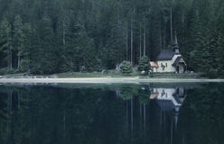 Old church and woodlands reflected in lake Stock Photos
