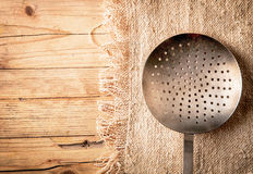 Old circular metal colander. Sieve or strainer with perforated holes for draining vegetables while preparing a meal in a country kitchen over a textured wooden Royalty Free Stock Images