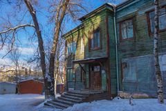 Old city barrack. Old wooden house, dilapidated building. In the yard there is snow, in the background there are iron garages. City line Stock Image