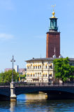 Old city church on water. Old red brick church on blue water under blue sky Stock Photography