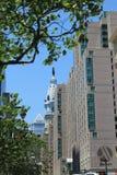 Old city hall tower among modern buildings Stock Photos