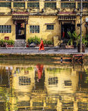 Old City,Hoi An,VieTnam. View abstract on the old town of Hoi An from the river.Monk is walking down the street of the old town and is reflected in the waters of Stock Photography
