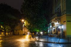 The old city of Lviv at night in the rain. With reflections on the wet pavement Royalty Free Stock Image