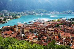 Old city and port of Kotor, turquoise water and boats. View over the old city and port of Kotor, with turquoise water and big boats docked on shore. The panorama stock photo