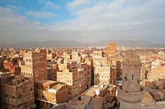The Old City of Sana'a, decorated houses, palace, minarets and Mosque in the fog, Yemen. The Old City of Sana'a, the oldest continuously inhabited and populated stock photo
