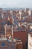 The Old City of Sana'a, decorated houses, palace, minarets and the Saleh Mosque in the fog, Yemen Stock Photo