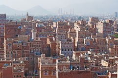 The Old City of Sana'a, decorated houses, palace, minarets and the Saleh Mosque in the fog, Yemen. The Old City of Sana'a, the oldest continuously inhabited and royalty free stock photography