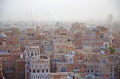 The Old City of Sana'a, decorated houses, palace, minarets and the Saleh Mosque in the fog, Yemen. The Old City of Sana'a, the oldest continuously inhabited and royalty free stock images