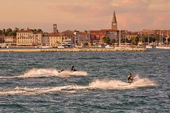 Old city by the sea with two watercrafts in the foreground. At sunset Royalty Free Stock Images