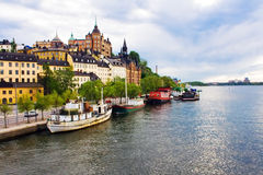Old city skyline under cloudy sky. Boats on water near old nordic city buildings under cloudy sky Royalty Free Stock Photo