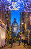 Old City street leading to st. Paul cathedral. Street view with evening lights and public house. LONDON, UK - DECEMBER 19, 2014: Old City street leading to st Royalty Free Stock Photography