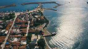 Old city with terra cotta tile rooftops drone aerial view. Small coast city near the sea with marina. Old city with terra cotta tile rooftops drone aerial view stock footage