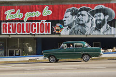Old Claaic Car driving by propoganda sign. Havana, Cuba- December 31, 2010; Old Classic car driving by a propoganda sign Todo por la REVOLUCION meaning All for Stock Image