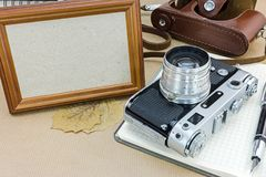 Old classic camera with leather case, empty photo frame, notepad Stock Images