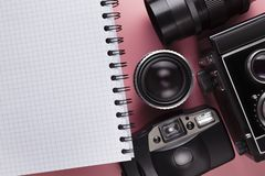 Old classic camera, lens and notebook with a blank page on a pink background. Old classic camera, lens and notebook with a blank page on a pink table background stock photos