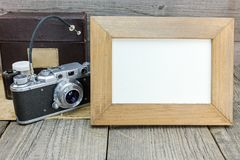 Old classic camera and photo frame on gray wooden background Royalty Free Stock Image