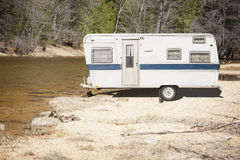 Old Classic Camper Trailer Near A River Royalty Free Stock Images