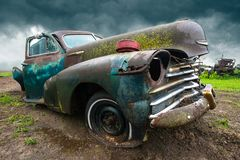Old Classic Car, Junk Yard. Old vintage retro Chevy classic car in a junkyard. The junk yard rust is from an old era for cars and automobiles. A rain storm is in Royalty Free Stock Photos