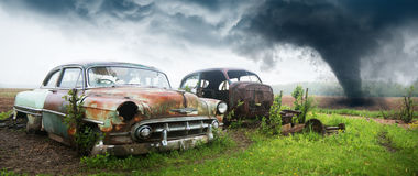 Old Classic Car, Junk Yard. Old vintage retro Chevy classic car in a junkyard. The junk yard rust is from an old era for cars and automobiles. A rain storm is in Stock Photo