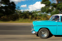 Old classic car on the road in Cuba with white clouds and blue s Royalty Free Stock Images
